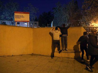 Dos menores saltan el muro del centro de acogida de Hortaleza para entrar, ayer, en el recinto.