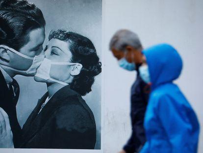 Unas personas protegidas con mascarilla pasan junto a una foto en la pared de un beso con mascarillas en Córdoba.