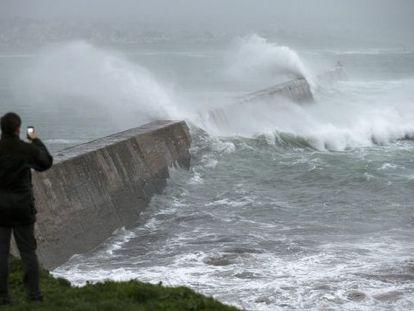 Un hombre fotografía las grandes olas que rompen en un muelle en Esquibien, en la zona oeste de Bretaña, Francia.