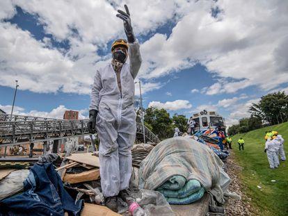 Trabajadores ferroviarios con mascarillas recogen basura dejada por personas sin hogar en las vías del tren en Bogotá.