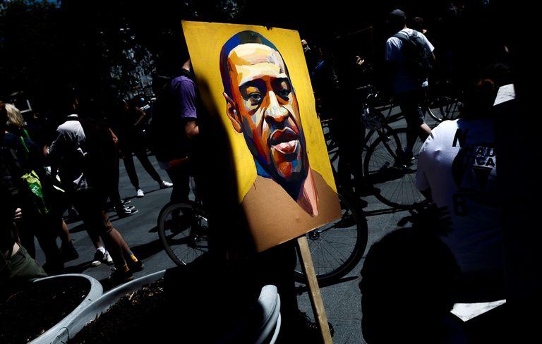 Un manifestante sostiene una imagen con el rostro de George Floyd, el afroamericano asesinado por un policía blanco en Nueva York.