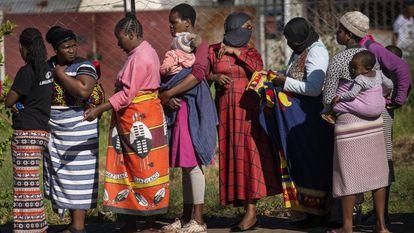 Una fila de mujeres, algunas con sus hijos a cuestas, esperan recibir comida en un barrio de Johannesburgo (Sudáfrica).