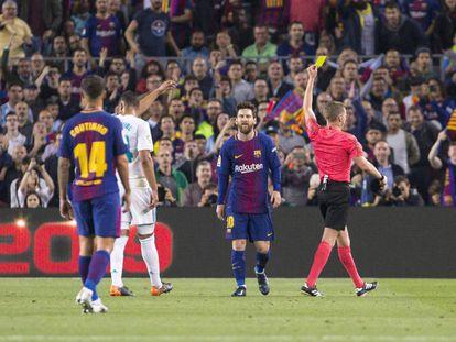 El árbitro muestra la amarilla a Messi durante el clásico.