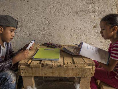 Justin, de 11 años, y Melani, de ocho, hijos de Delmi Judith Muralles Rodríguez, de 30 años, hacen los deberes en su casa en Potrero Grande (Guatemala) siguiendo las pautas didácticas recibidas poco antes del Ministerio de Educación.