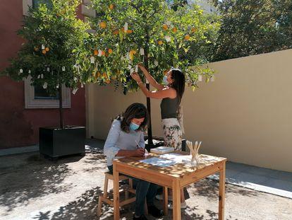 Dos visitantes cuelgan sus deseos en 'Wish Tree', el proyecto de Yoko Ono que se expone en el museo Lázaro Galdiano, en Madrid. I.U