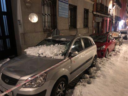 Varios coches con las lunas rotas por la nieve de los tejados tras el paso de 'Filomena' en la calle San Andrés del barrio de Malasaña.