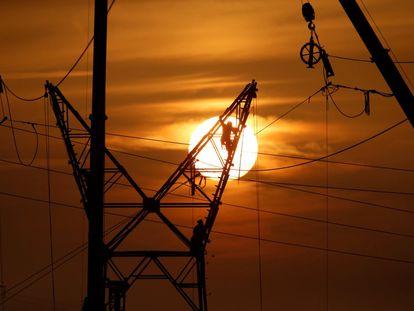 Los técnicos trabajan en una torre de electricidad durante el mantenimiento de las líneas eléctricas de alta tensión.