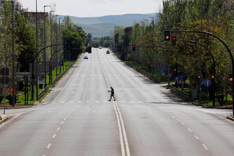 Un hombre camina por una avenida desierta de Córdoba.