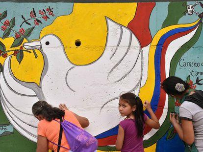 Dos colombianas pintan un mural por la paz.