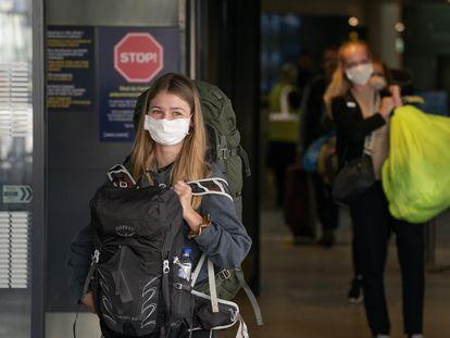 Una joven se protege del coronavirus con una mascarilla.