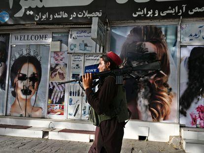 Un talibán pasa por delante de un salón de belleza con las imágenes de mujeres pintadas con aerosol, en Kabul este 18 de agosto.
