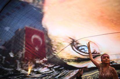 Una manifestante bajo un inmenso retrato de Mustafa Kemal Atatürk, fundador de la Turquía republicana y laica, en una concentración contra el golpe de Estado en la localidad turca de Esmirna organizada el 4 de agosto por la oposición socialdemócrata.