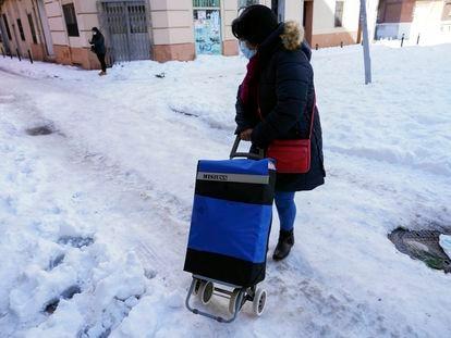 Una mujer regresa a casa tras hacer la compra días después del Temporal Filomena