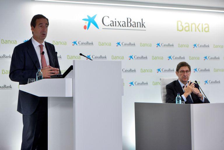 El presidente de Bankia, que será presidente ejecutivo de la nueva entidad, José Ignacio Goirigolzarri (derecha), y del consejero delegado de CaixaBank, Gonzalo Gortázar. EFE/David Campos
