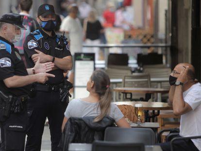 Dos agentes de la pollcía local de A Coruña se dirigen a un hombre que se encontraba fumando en una terraza de un bar de la ciudad.