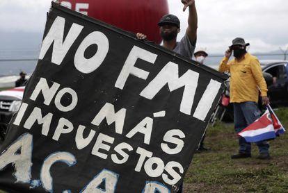 Un hombre participa junto a cientos de personas en una protesta por las inmediaciones del aeropuerto Juan Santamaría, el miércoles 14 de octubre en San José (Costa Rica).