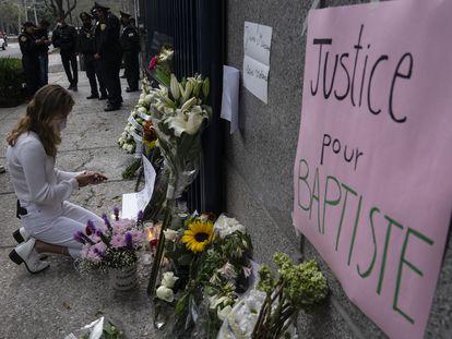 Una joven deposita un cartel en un altar en homenaje al empresario franco mexicano Baptiste Lormand en la Embajada de Francia.