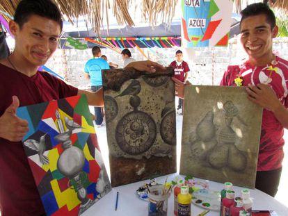 Waldo Flores (i) y otro joven muestran sus pinturas.