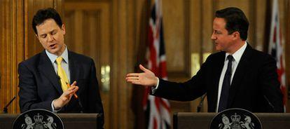 El primer ministro británico, David Cameron (derecha), cede la palabra al viceprimer ministro Nick Clegg, ayer en Londres.