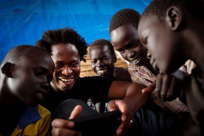 El 26 de noviembre de 2015, Ishmael Beah, ex niño soldado, muestra algunas fotos de su móvil a niños en un centro de protección de la infancia en Juba, Sudán del Sur.