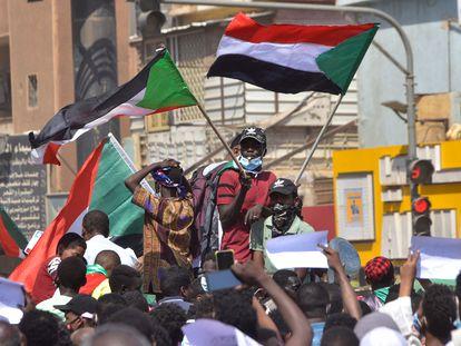 Manifestantes sudaneses ondean banderas nacionales en una marcha de apoyo al Gobierno civil, en Jartum este jueves.
