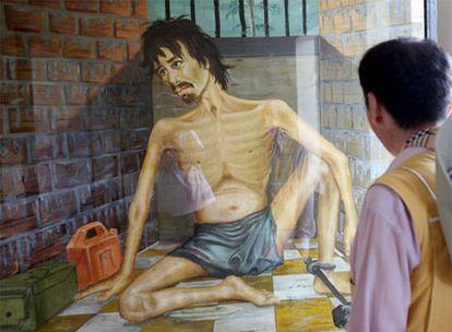 Un turista contempla un cuadro pintado por el artista Vann Nath, en el museo Tuol Sleng, en Phnom Penh, en Camboya.