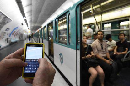 Un hombre sujeta un móvil en el metro de París