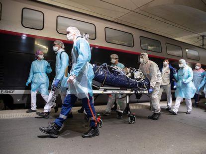 Personal sanitario traslada a un paciente de Covid-19 para subirlo a un tren de alta velocidad medicalizado en la estación de Austerlitz, en París.