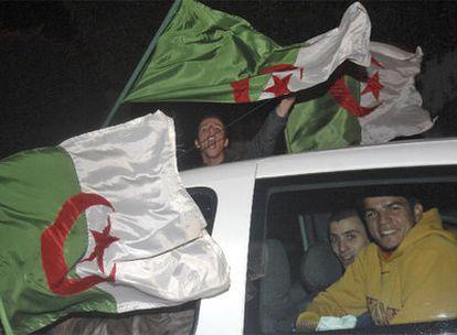 Jóvenes argelinos exhiben banderas nacionales por las calles de Argel.