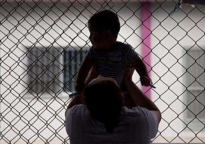 Una prisionera juega con su hijo en el patio de la prisión.
