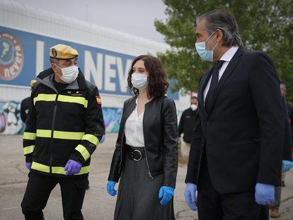 La presidenta de la Comunidad de Madrid, Isabel Díaz Ayuso, con un militar de la Unidad Militar del Ejército y con el consejero de Sanidad de la Comunidad de Madrid, Enrique Ruiz Escudero, durante la clausura de la morgue del Palacio de Hielo de Majadahonda, esta semana.