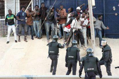 Los antidisturbios intenta controlar a los inmigrantes que han saltado la valla.