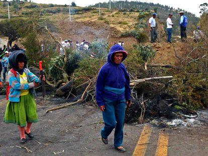 Un grupo de indígenas bloquea un camino en señal de protesta.