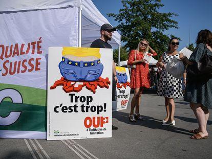 Militantes de la derecha nacionalista suiza junto a un cartel de la campaña para frenar la inmigración, el 13 de septiembre en Ginebra.