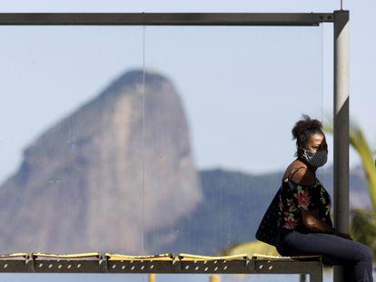 Una mujer espera este lunes en una parada de autobús cerca de Río de Janeiro.