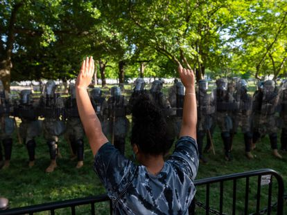 A protestor raises her hands near a line of National Guard soldiers deployed near the White House on June 1, 2020 as demonstrations against George Floyd's death continue. - Police fired tear gas outside the White House late Sunday as anti-racism protestors again took to the streets to voice fury at police brutality, and major US cities were put under curfew to suppress rioting.With the Trump administration branding instigators of six nights of rioting as domestic terrorists, there were more confrontations between protestors and police and fresh outbreaks of looting. Local US leaders appealed to citizens to give constructive outlet to their rage over the death of an unarmed black man in Minneapolis, while night-time curfews were imposed in cities including Washington, Los Angeles and Houston. (Photo by ROBERTO SCHMIDT / AFP) / ALTERNATE CROP