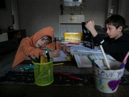 Dos niños estudiando en una casa de Madrid.