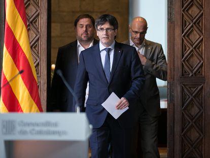El entonces presidente Carles Puigdemont, acompañado de los consejeros Oriol Junqueras (izquierda) y Raül Romeva, en marzo de 2017.