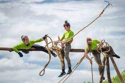 Tres concursantes intentan superar una prueba en la que tienen que pasar de una portería a otra con cuerdas.