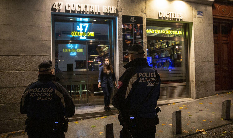 Una pareja de policías municipales controla el cierre de los bares de la zona de La Latina, en el centro de Madrid, primera noche de toque de queda.