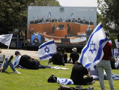 Manifestantes israelíes siguen las deliberaciones del Supremo sobre Netanyahu en una pantalla, este domingo en Jerusalén.