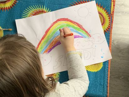 Una niña dibuja un arcoíris.