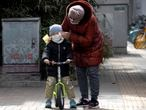 A woman wipes the face of a child on the streets of Beijing on Thursday, March 12, 2020. For most people, the new coronavirus causes only mild or moderate symptoms. For some it can cause more severe illness, especially in older adults and people with existing health problems. (AP Photo/Ng Han Guan)