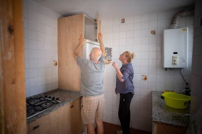 Joaquín Fontiberio ayuda a montar la cocina de la que va a ser su casa, junto a la voluntaria Raquel Sáez.
