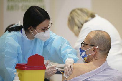 Una sanitaria vacuna a un hombre en Roma el 10 de marzo.