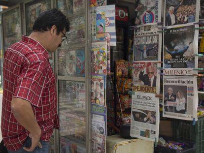 Un hombre observa las portadas de los periódicos en un kiosko de prensa.