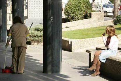 Una limpiadora recoge colillas mientras otra mujer fuma en la vía pública en Madrid.