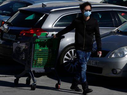 Un hombre lleva una mascarilla en el aparcamiento de un centro comercial en Rivas Vaciamadrid.