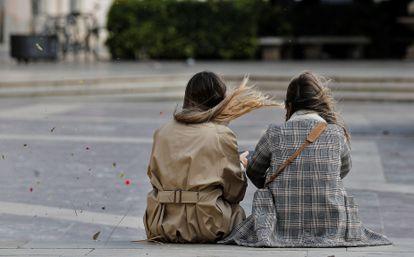 Dos jóvenes, este mediodía, en la plaza de la Virgen de Valencia.