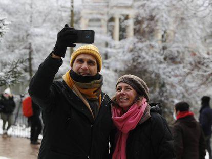 Dos personas se toman una foto en el Retiro, en Madrid, durante la nevada.